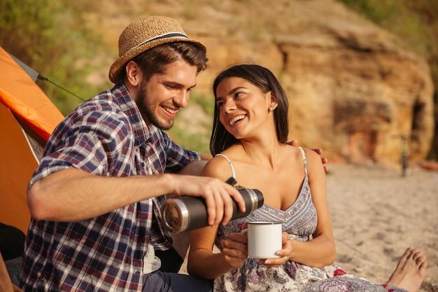 Jovem casal bebendo chá quente na fogueira enquanto acampa na praia