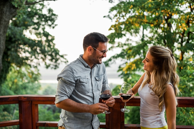 Jovem casal bebendo vinho no terraço ou varanda na floresta.