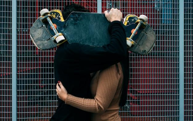Jovem casal beija se escondendo atrás do skate. conceito de amor. conceito de esporte urbano.