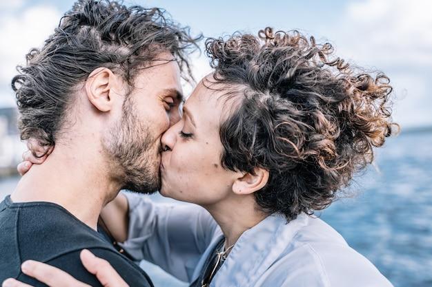 Jovem casal beijando com o mar sem foco