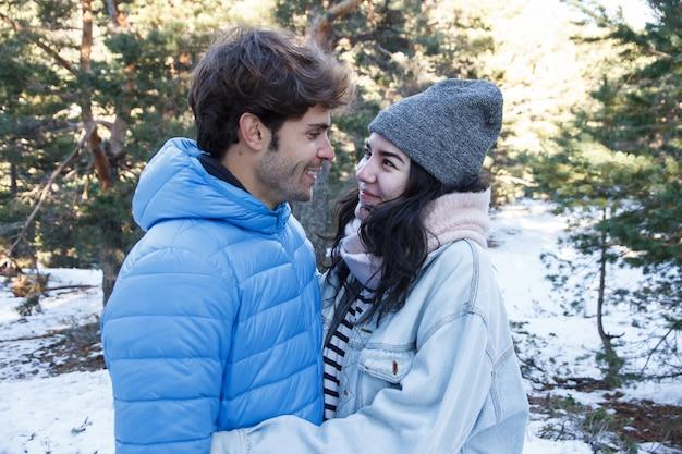 Jovem casal beijando nas montanhas em um dia nevado.