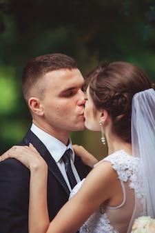 Jovem casal beijando no vestido de casamento. noiva segurando o buquê de flores