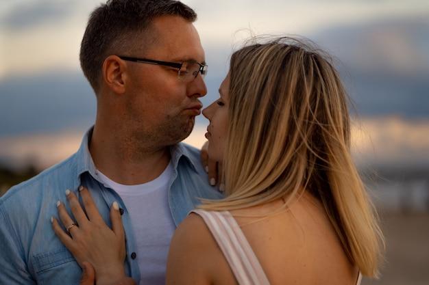 Jovem casal bonito caucasiano feliz no pôr do sol na praia no verão.
