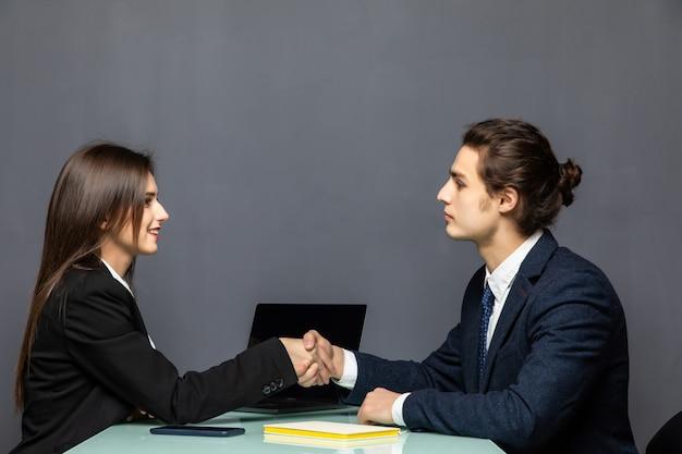Jovem casal bonito de trabalhadores de negócios sorrindo felizes e confiantes, apertando as mãos com sorriso no rosto para acordo no escritório em cinza
