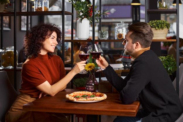 Jovem casal bonito em um restaurante, lanchonete, com copos de vinho tinto, mulher morena, cabelos cacheados. o conceito de emoções engraçadas.