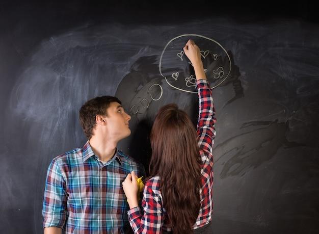 Jovem casal branco com camisa quadriculada desenhando algo no quadro negro.