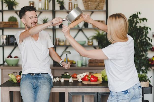 Jovem casal brigando com caçarola e rolo na cozinha