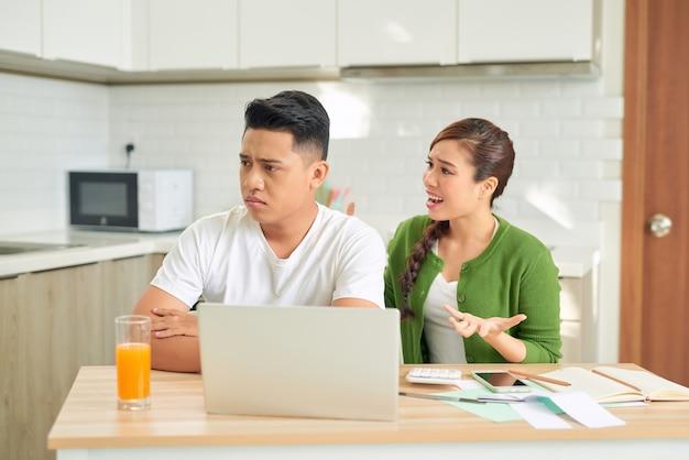 Jovem casal brigando com contas não pagas na sala de estar