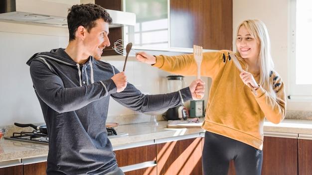 Jovem casal brigando com espátula de madeira; colher e bata na cozinha
