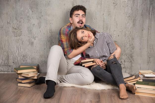 Jovem casal brigando de brincadeira um com o outro ao lado de livros