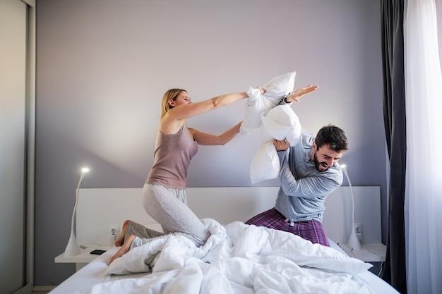 Jovem casal brincalhão tendo travesseiro luta de manhã no quarto