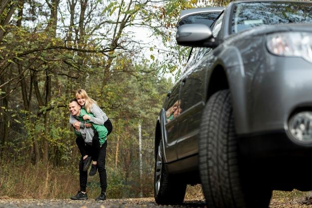 Jovem casal brincando atrás de um carro