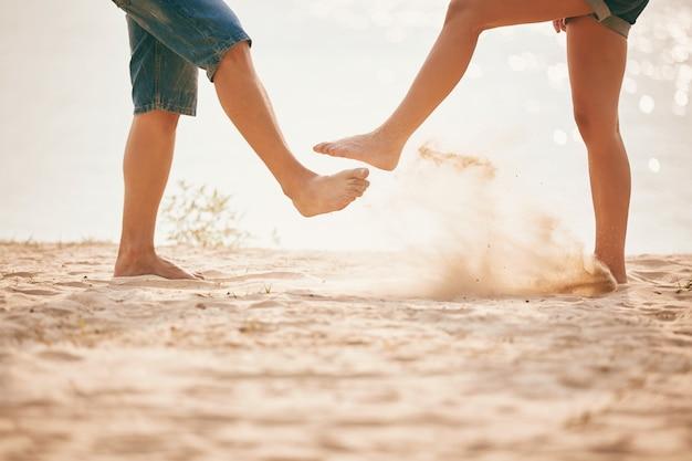 Jovem casal brincando com areia. estilo de vida de verão.