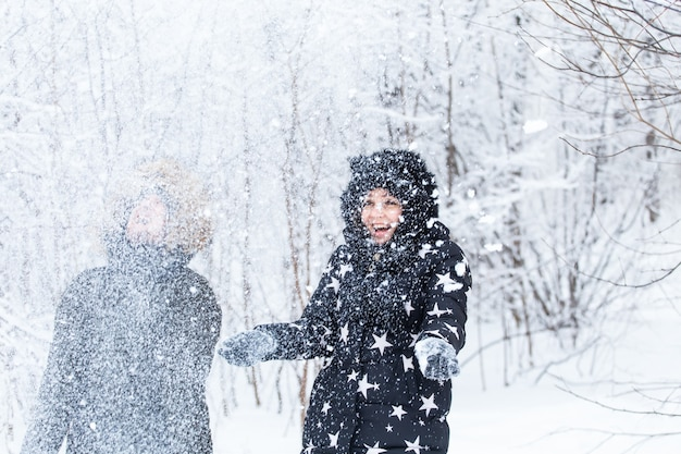 Jovem casal brincando com neve em winter park.