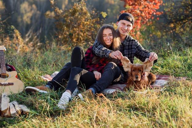 Jovem casal brincando com seu cão de estimação em piquenique no parque.
