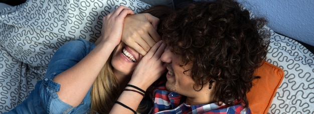 Jovem casal brincando e rindo deitado na cama