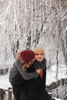 Jovem casal brincando na paisagem de inverno