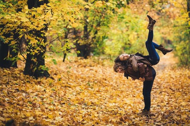 Jovem casal brincando no parque outono.