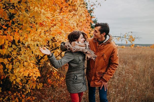 Jovem casal caminha na floresta de outono entre árvores coloridas
