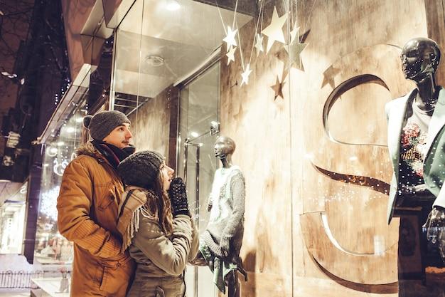 Jovem casal caminhando no centro da cidade e vitrines à noite.