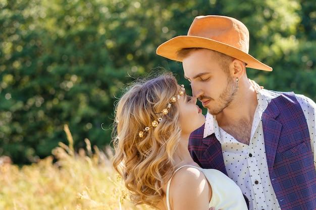 Jovem casal cara e menina no campo abraçando, conceito de relacionamento romântico