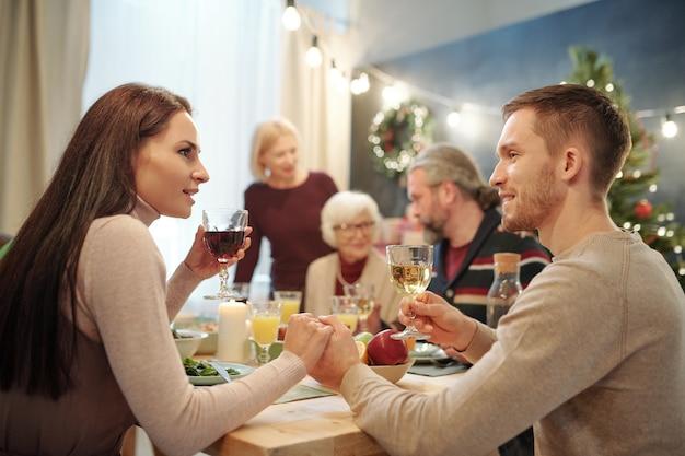 Jovem casal carinhoso com taças de vinho fazendo um brinde festivo na mesa servida