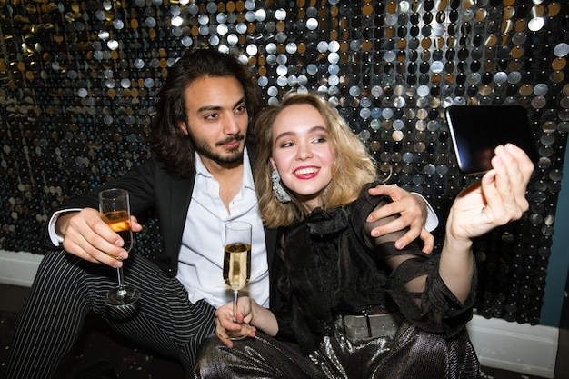 Jovem casal carinhoso e feliz em um traje glamoroso fazendo selfie com uma parede brilhante em uma boate na festa