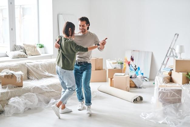 Jovem casal carinhoso em trajes casuais dançando na sala de estar após se mudar para um novo apartamento ou casa com coisas embaladas no fundo