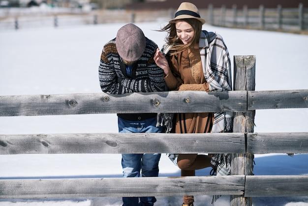 Jovem casal carinhoso feliz parado perto de uma cerca de madeira em ambiente rural, enquanto conversa ao ar livre em um dia de inverno