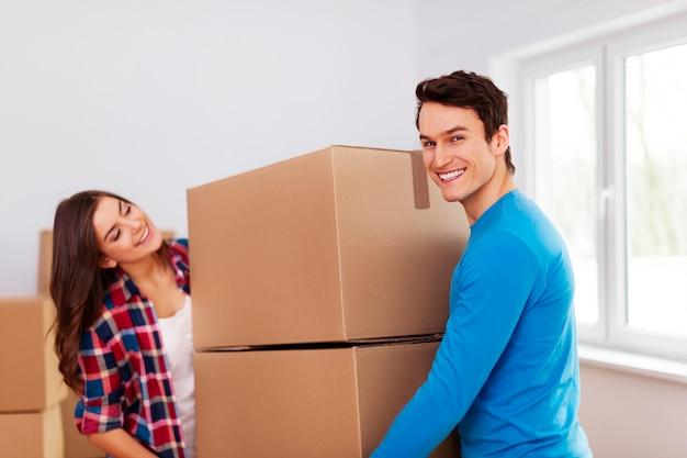 Jovem casal carregando caixas
