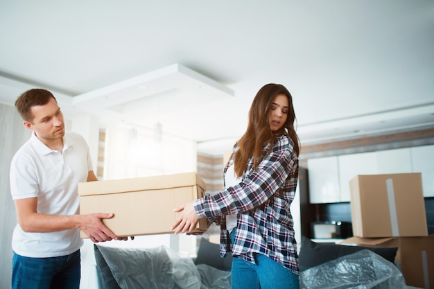 Jovem casal carregando grande caixa de papelão na nova casa.
