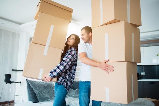 Jovem casal carregando muitas caixas de papelão, um por um na nova casa. mudança de casa.