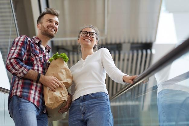 Jovem casal carregando sacola de compras