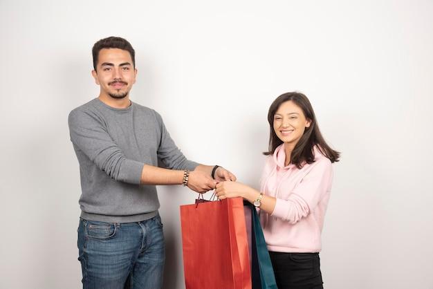 Jovem casal carregando sacolas de compras em branco.