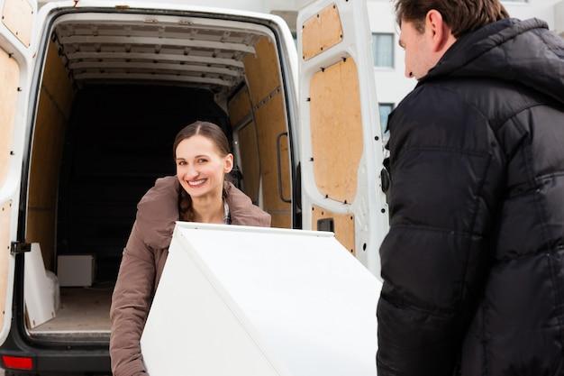 Jovem casal carregando um caminhão em movimento