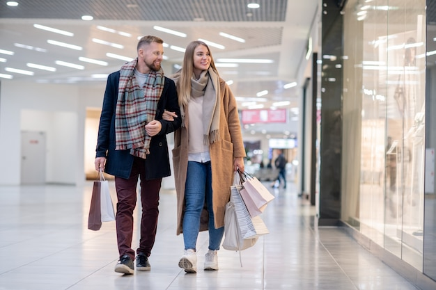 Jovem casal casual com sacos de papel olhando para as roupas na vitrine da loja enquanto passa depois das compras
