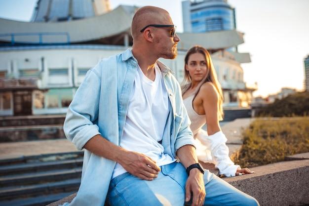 Jovem casal caucasiano bronzeado, história amorosa moderna em efeito de grão de filme e estilo vintage. hora do pôr do sol. caminhando pelas ruas da cidade, tarde quente de verão. conceito de lua de mel. tons de laranja azul-petróleo.