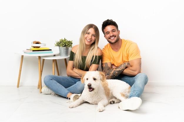 Jovem casal caucasiano com cachorro ficando em casa de braços cruzados enquanto sorri