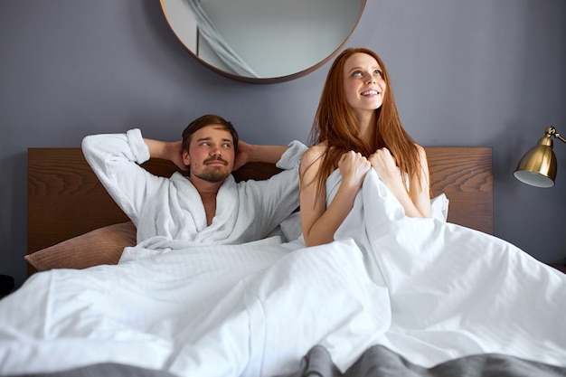 Jovem casal caucasiano deitado na cama feliz após a intimidade