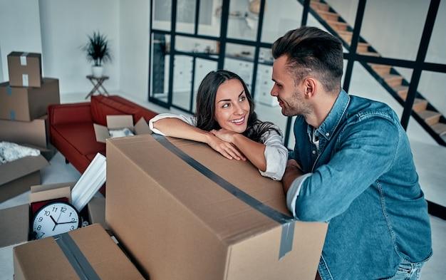 Jovem casal caucasiano embalagem caixa de papelão para se mudar para apartamento novo.