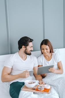 Jovem casal caucasiano feliz apaixonado, tomando café da manhã na cama e assistindo vídeos no tablet.