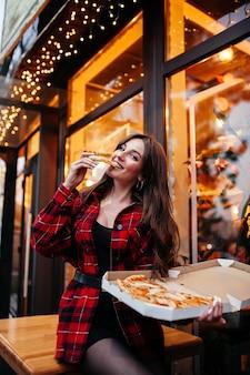 Jovem casal caucasiano feliz sentado à mesa, desfrutando de pizza recém-assada eu