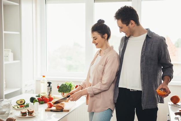 Jovem casal caucasiano preparando comida na cozinha, fatiando frutas e vegetais