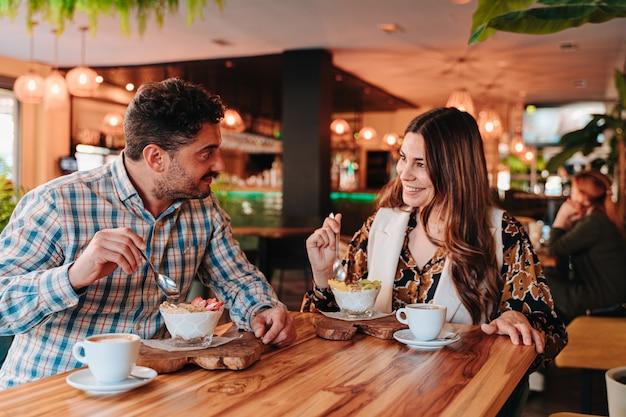 Jovem casal caucasiano tomando café da manhã, um café colombiano e uma mistura de iogurte de frutas para uma dieta em um restaurante
