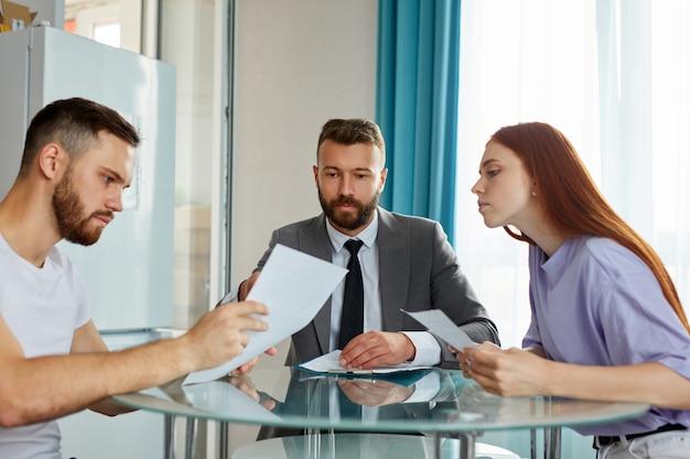 Jovem casal caucasiano visitando advogado profissional