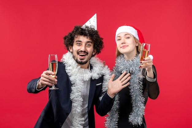 Jovem casal celebrando o ano novo nas férias de amor de natal de parede vermelha