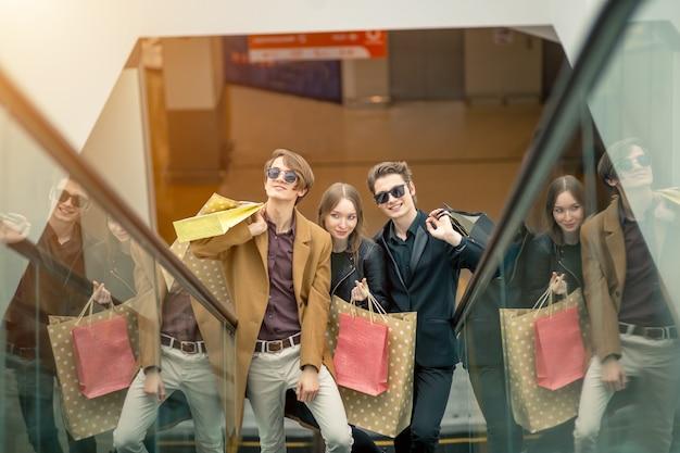 Jovem casal chappy com sacos de compras descendo pela escada rolante e apontando o dedo no shopping
