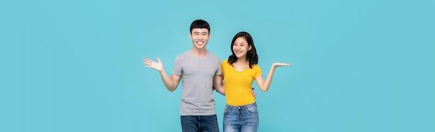Jovem casal chinês asiático abraçados e sorrindo com o gesto da mão aberta