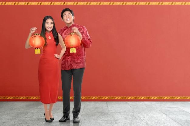 Jovem casal chinês com vestido tradicional segurando lanternas vermelhas