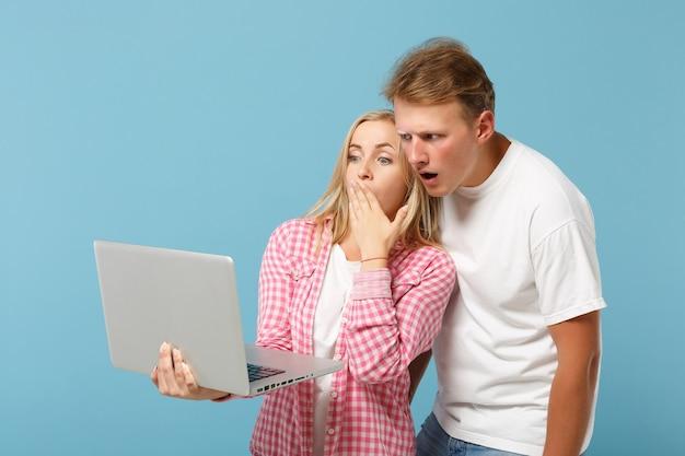 Jovem casal chocado, amigos, homem e mulher, em camisetas brancas rosa posando
